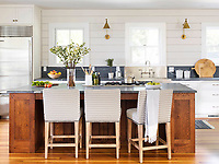 The stylish kitchen has painted wood panelling on the walls and a wood floor. An island unit provides a central cooking area and doubles as a breakfast bar.