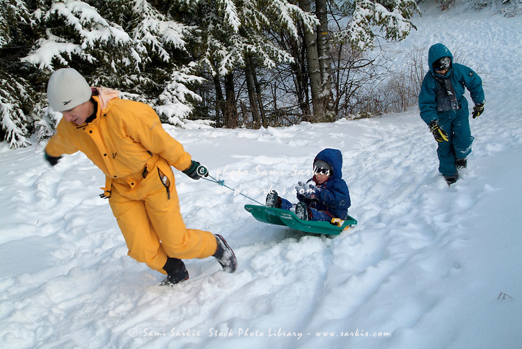 Mother and her two children playing with a sled in the snow at a ski resort in the French Alps, France.