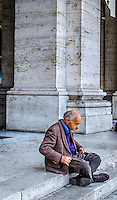 Urban Street Photography. Rome Italy.<br /> The ancient pillars of this building work as a complimentary backdrop for this old man sitting alone on the steps. <br /> He looks old, hunched over, and tired. Yet the ancient pillars look straight and strong as the day they were built.