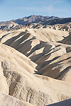 Death Valley National Park, California; a view of the erosional multi-colored rock formations  that make up the badlands around Zabriskie Point, which were formed by sediment from the long extinct Furnace Creek Lake, in late afternoon sunlight and shadows