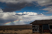 In Nevada's northern desert a rainbow graces a cloudy-blue sky next to an abandoned building near a rest area along the Interstate.