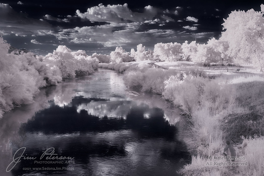 Looking Downstream (Infrared).  The Jordan River (the one in Utah, not the one in the Middle East) flows northward through the Salt Lake Valley and empties into the Great Salt Lake.  It is surrounded by Salt Lake City and its suburbs for most of its length, and was thus once highly polluted (though that has since been cleaned up to a considerable degree).  Much of it is now bordered by parkland with walking and cycling paths, and it's even visited by the occasional fisherman (seen in the lower right corner here).<br /> <br /> Image ©2021 James D. Peterson<br /> <br /> Tech info: Nikon D3200 camera (modified for infrared with 590nm filter), Nikon 18-140mm lens at 23mm, 1/250 sec. at f11, ISO 400.