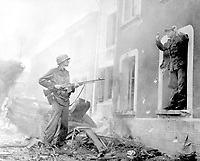 """""""Finally, I got me a 'souvenir.'  Somehow the Jerries I got in my sights always seemed to have bad luck.  Then one day in Illy, France, I spotted an officer inside a battered building and I yelled for him to come on out.  He did.""""  Ca. September 1944.  Army. (OWI)<br /> Exact Date Shot Unknown<br /> NARA FILE #:  208-YE-54<br /> WAR & CONFLICT BOOK #:  1053"""