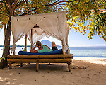 A guest relaxes in one of several beach-front cabana beds at Siladen Resort and Spa, on Siladen Island in the Bunaken National Park off North Sulawesi, Indonesia.  She is facing Bunaken Island and the volcano island Manado Tua.