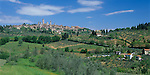 Tuscany, Italy:  The distant hill town of San Gimignano rises above nearby vineyards and olive groves