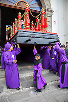 Antigua, Guatemala.  Cucuruchos Gently Move an Anda out of San Jose Cathedral to begin a March through the Town, Semana Santa.