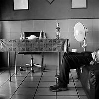 A man sits on a sofa at the Harlequins Sport Bar on Pretoria Street.