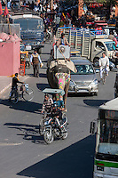 Jaipur, Rajasthan, India.  Mid-day Traffic in Downtown Jaipur.  A Mahout Directs his Elephant Using a Long Pole.