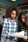 HIgh School Classroom two female students discussing how to proceed on joint project
