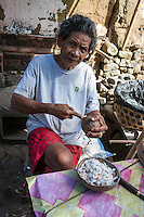 Bali, Indonesia.   Woman Removing Coconut from inside a Coconut Shell.  Tenganan Village.