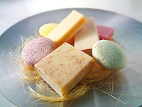 selection of natural hand made scented soap bars piled on an aluminium dish.