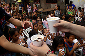 Some children eat while other volunteers from the Project Pearl distribute portions of food in the slums of Smokey Mountain-II in Manila in Philippines. Photo: Sanjit Das