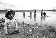 In Bolivia, on the banks of Lake Titicaca, children are employed as fishermen - Child labor as seen around the world between 1979 and 1980 – Photographer Jean Pierre Laffont, touched by the suffering of child workers, chronicled their plight in 12 countries over the course of one year.  Laffont was awarded The World Press Award and Madeline Ross Award among many others for his work.