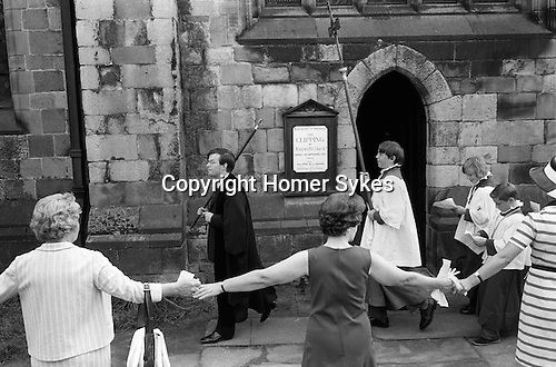 """Wirksworth Derbyshire St Marys Church Clipping   September 1973.<br /> <br /> The congregation hold hands in a circle around the whole of the church. The word """"clipping"""" is Anglo-Saxon in origin, and is derived from the word """"clyp-pan"""", meaning """"embrace"""" or """"clasp"""" and thus is an expression of devotion."""