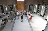 In the circular winery vat hall with stainless steel fermentation tanks, a bottling line and a filter, and a group of visiting wine enthusiasts listening to Laurent Cogombles, owner and winemaker Chateau Bouscaut Cru Classe Cadaujac Graves Pessac Leognan Bordeaux Gironde Aquitaine France