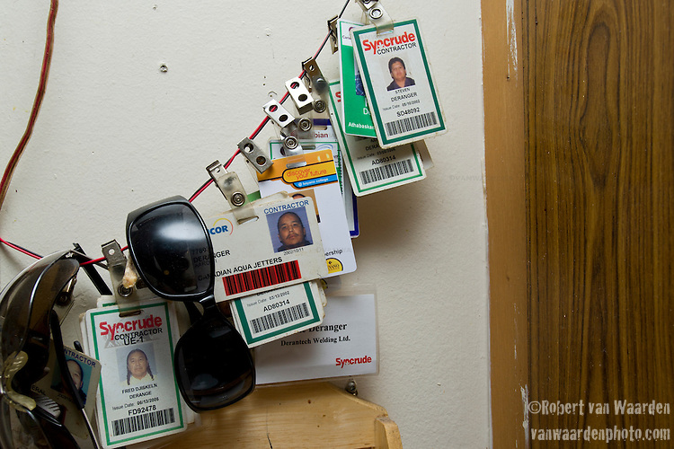 The contractor badges of the Deranger family hang on a wire in the kitchen. Despite objections to Tar Sands development, many First Nations peoples find themselves working within the industry to support themselves or their family. It is often the only opportunity they have to survive. The fear is that when the Oil companies leave, they will not be able to return to their traditional way of living and there will be nothing left.