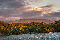 Aoraki Mount Cook emerging from behind clouds at sunset on Gillespies Beach, Westland Tai Poutini National Park, UNESCO World Heritage Area, South Westland, New Zealand, NZ