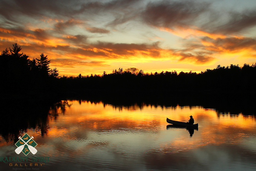 """""""Sunset Paddle""""<br /> <br /> The canoeist enjoys a sunset paddle on a beautiful Fall evening in the Boundary Waters Canoe Area Wilderness (BWCAW).<br /> <br /> Award: This image has been juried into the Wilderness Forever Exhibit at the Smithsonian National Museum of Natural History, 2014-2016. The exhibit celebrates the 50th anniversary of the Wilderness Act. This photograph was the winner in its class/division, """"People in Wilderness"""", amateur. It was also published in a special golden edition of Nature's Best Photography magazine, along with the story Dawn provided. We're pleased that Minnesota's wilderness is part of the Wilderness 50 celebration. <br />  <br /> There were more than 5500 entries, 300 semi-finalists (2 of which were Dawn's, this one and """"Through the Fog""""), and 50 images are on exhibit in large format at the Smithsonian -- one of which is Sunset Paddle from the Boundary Waters."""