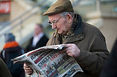 A man with a cigar reads the Racing Post before placing a bet at Doncaster racecourse