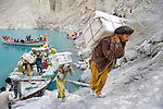 Hunza District, Pakistan.  Sept 24, 2010.  Workers carry goods off a boat up a mountain of dirt and rocks.  The packages will be loaded on to trucks waiting on the KKH on the other side of the hill.  The lake was created by a landslide in January, 2010, which buried several villages along the Hunza River, as well as the Karakoram Highway, the major link between China and Pakistan.  Now goods and people are transported by boats that were brought up from Karachi.  Photo by Ellen Jaskol.