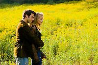Couple embracing in front of goldenrod