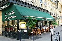 The restaurant brasserie Le Noailles with a traditional French outside terrasse seating with wicker chairs. People eating and having a drink, a woman walking by in white trousers pants, a green sun shade, Bordeaux City, Bordeaux Gironde Aquitaine France Europe
