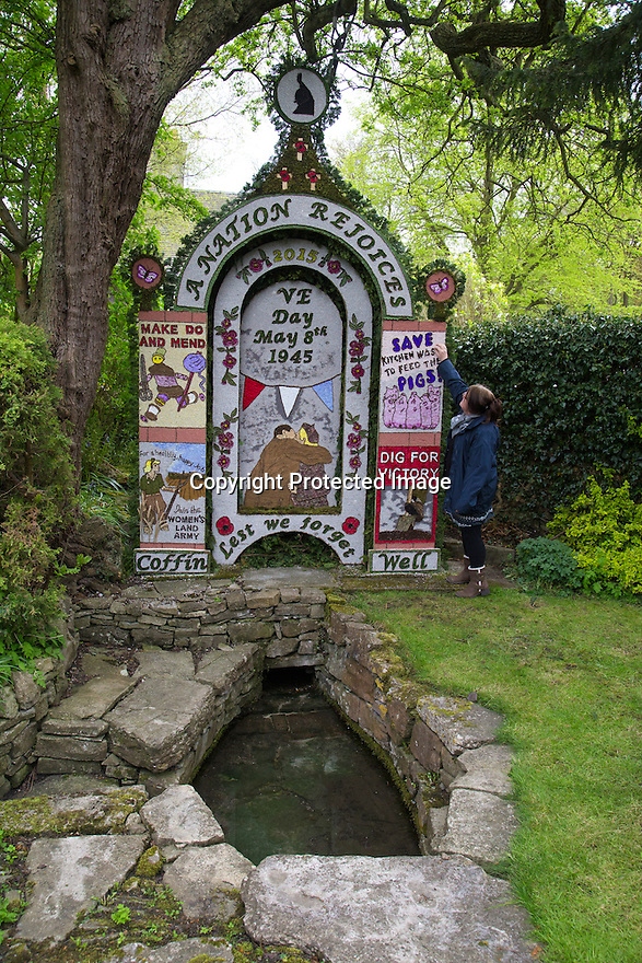 14/05/15<br /> <br /> Diane Wilton puts the finishing touches to her V.E. Day inspired design, at Coffin Well named after the shape of the well.<br /> <br /> To mark ascension day this year's well dressings are unveiled and blessed by the local clergy in the Derbyshire village of Tissington in the Peak District National Park.<br /> <br /> Before today's blessings, wooden boards coated in clay are decorated with tens of thousands of petals, leaves and pieces of foliage to create the giant intricate mosaics. The boards,  take teams of many villagers three days to make. <br /> <br /> The village has been decorating its six wells every year for more than six hundred years. The tradition is believed to be a celebration of the wells never running dry, giving life and  sustaining the village during times of plague. After a church service today (Thursday)  clergy from six parish will bless each of the well.  <br /> <br /> Following in Tissington's footsteps many other villages in the Derbyshire area also have their own well dressing traditions.<br /> <br /> <br /> All Rights Reserved: F Stop Press Ltd. +44(0)1335 418629   www.fstoppress.com.