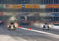 Apr 26, 2014; Baytown, TX, USA; NHRA top fuel driver Tony Schumacher (left) races alongside Brittany Force during qualifying for the Spring Nationals at Royal Purple Raceway. Mandatory Credit: Mark J. Rebilas-
