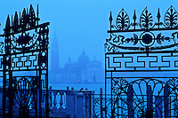 Italy, Venice. View of San Giorgio Maggiore from The Giardinetti Reali (royal gardens) framed  through an iron gate