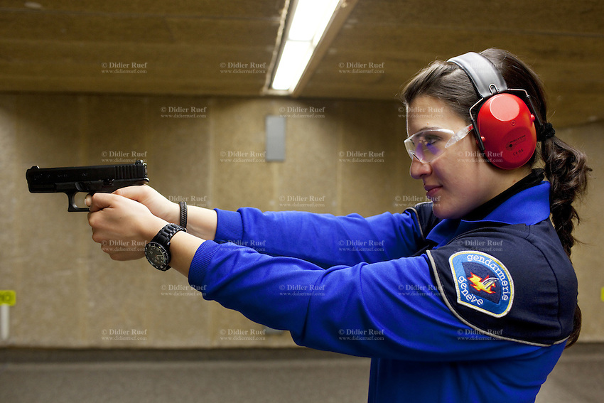 Switzerland. Geneva. A female police officer is aiming her Glock hand gun at firing range. The policewoman is training at the Police education center (Centre de formation de la Police. CCFP). She is using a Glock pistol which is a semi-automatic pistol designed and produced by Glock Ges.m.b.H. Glock was the first manufacturer to introduce ferritic nitrocarburizing into the firearms industry as an anti-corrosion surface treatment for metal gun parts. 22.03.12 © 2012 Didier Ruef