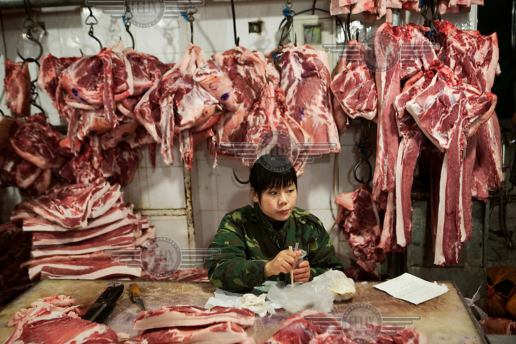 Butcher selling pork takes a break at Beijing's wet market. Pork prices have doubled in less than a year in China, reaching dangerously high levels for the average citizen. Government officials have since announced direct controls on food prices; requiring large producers of pork and other staple products to obtain government approval before raising prices.