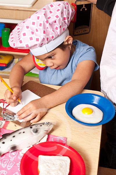 Education Preschool 3-4 year olds pretend play girl wearing chef's hat taking telephone order in restaurant