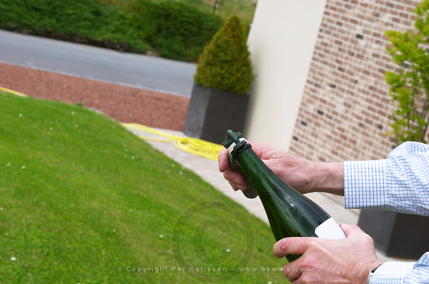 Herve Jestin, oenologist and chief winemaker holding a bottle of champagne Beuverie 1983 vintage that he will disgorge manually. The first step is to hold the bottle pointing upwards and remove the capsule cork Champagne Duval Leroy, Vertus, Cotes des Blancs, Champagne, Marne, Ardennes, France
