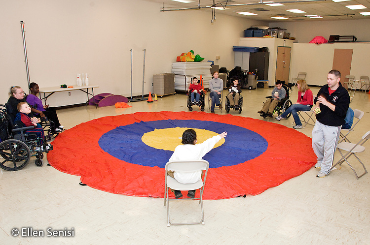 MR / Albany, NY.Langan School at Center for Disability Services .Ungraded private school which serves individuals with multiple disabilities.Special education students with teachers and teaching assistants in Adaptive Physical Education class (APE) play a game. Objective of game is to throw soft dice as close to the center of bulls eye as possible and to count the number of dots on the top of the die as it lands..MR: AH-cfds.© Ellen B. Senisi