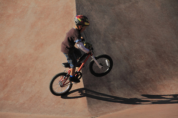 Boy riding his bike in a skateboard park in Denver, Colorado.