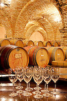 Wine aging in barrels in cellar with wine glasses. Castello di Amorosa. Napa Valley, California. Property relased