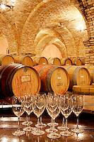 Wine aging in barrels in cellar with wine glasses. Castello di Amorosa. Napa Valley, California. Property relased