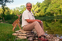 Orphaned fawn in rehabilitation at private home seeks company of human family when both caught by surprise by camera
