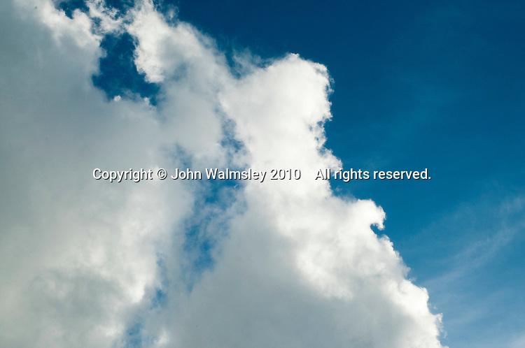 Cumulus clouds and a few cirrus clouds high beyond.