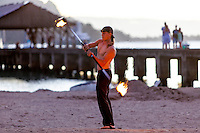 Male fire dancer performing on the beach in Hanalei, Kaua'i