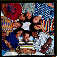SETUP SHOT OF GROUP OF MULTI-ETHNIC TEENS LYING HEADS TOGETHER ON A MAP OF THE WORLD. TEENAGERS. OAKLAND CALIFORNIA USA.