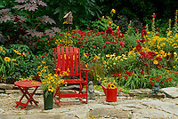 Bright red and yellow garden with matching furniture and whimsical garden art-- animals statues, birdhouse, and cut flowers