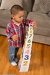 Two year old toddler boy building with cardboard stacking cubes, placing smallest block on top of tower