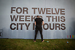 """© Joel Goodman - 07973 332324 . 05/06/2015 . Manchester , UK . A man urinates against a poster reading """" For twelve weeks this city is ours """" . Evening concerts featuring headliners , The Courteeners , playing a homecoming gig , at Heaton Park in Manchester in front of 25,000 people , the evening before the Parklife music festival . Photo credit : Joel Goodman"""