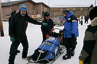Friday March 9, 2007   ----  Shageluk residents Rodger and Arnold Hamilton check in Jason Barron's team on Friday afternoon.
