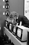 Sales assistant waiting for customers watching TV in department store. 1970S London