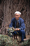man (senior) wearing traditional white head turban cleans pod vegetable; rural China near Zhongxian; culture; 041903