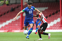 Kieffer Moore of Wigan shakes off a challenge from Brentford's Rico Henry during Brentford vs Wigan Athletic, Sky Bet EFL Championship Football at Griffin Park on 4th July 2020