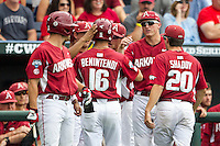 Arkansas Razorbacks outfielder Andrew Benintendi (16) is greeted by his teammates after driving in a run with a sacrifice fly against the Virginia Cavaliers in Game 1 of the NCAA College World Series on June 13, 2015 at TD Ameritrade Park in Omaha, Nebraska. Virginia defeated Arkansas 5-3. (Andrew Woolley/Four Seam Images)