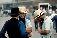 At the community market three young Amish men talk and joke. Amish men. Kidron Ohio United States market.